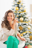 Portrait of happy young woman sitting near christmas tree Stock Image