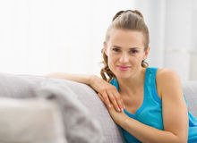 Portrait of happy young woman sitting on sofa Stock Photography