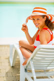 Portrait of happy young woman sitting on sunbed Stock Photo