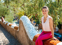 Portrait of happy young woman sitting on trencadis style fence. Get inspired by Park Guell in your next trip to Barcelona, Spain. Portrait of happy young woman Royalty Free Stock Photos