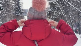 Portrait of a happy young woman smiling into frame while walking through the winter city. Open. Slow motion stock video