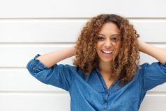 Portrait of a happy young woman smiling with hands in hair Stock Image