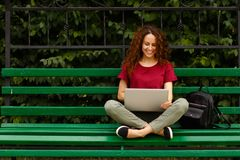 Portrait of a happy young woman smiling using laptop,sitting on bench in park. Lifestyle concept. Shooping online. stock photography