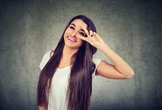 Happy young woman standing giving a peace gesture. Portrait of a happy young woman standing giving a peace gesture isolated on gray background stock images