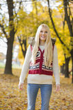 Portrait of happy young woman standing in park during autumn Royalty Free Stock Photos