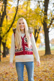 Portrait of happy young woman standing in park during autumn Royalty Free Stock Photo