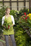 Portrait of a happy young woman standing with potted plant in greenhouse Royalty Free Stock Images