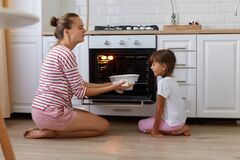 Portrait of happy young woman taking baking out of oven, her daughter looking at tasty sweets, people wearing casual clothing,