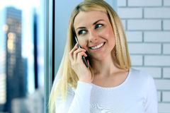 Portrait of happy young Woman Talking On Mobile Phone, standing near with window Stock Image