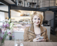 Portrait of happy young woman using cell phone in cafe Royalty Free Stock Photos