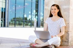 Portrait of a happy young woman using laptop computer outdoors Stock Images