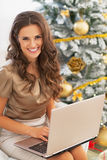 Portrait of happy young woman using laptop near christmas tree Royalty Free Stock Images