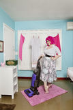 Portrait of a happy young woman vacuuming carpet Stock Photo