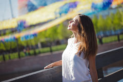 Portrait of happy young woman on a walk. Enjoy the sun. Place for your text on the left Stock Photography