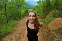 Portrait of happy young woman walking by mountain on Pico do Jaragua, Brazil.  stock photo