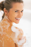 Portrait of happy young woman washing in bathtub Royalty Free Stock Photo