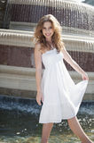 Portrait of happy young woman in white halter neck dress standing by water fountain Stock Image