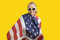Portrait of happy young woman wrapped in American flag over yellow background Royalty Free Stock Photography