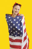 Portrait of happy young woman wrapped in American flag over yellow background Royalty Free Stock Photos