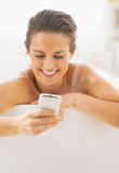 Portrait of happy young woman writing sms while in bathtub Stock Photography