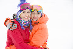 Portrait of happy young women in warm clothing embracing outdoors Stock Images