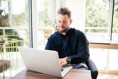 Portrait of happy young writer typing new book on laptop in office. Portrait of happy young writer typing new book on laptop Royalty Free Stock Image