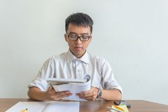 Portrait of hard-studying Asian student reading book stock photos