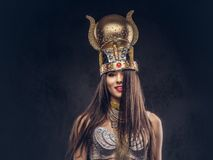 Portrait of haughty Egyptian queen in an ancient pharaoh costume. Isolated on a dark background Royalty Free Stock Photo