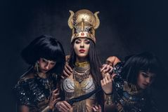 Portrait of haughty Egyptian queen in an ancient pharaoh costume with two concubines. Isolated on a dark background Royalty Free Stock Image