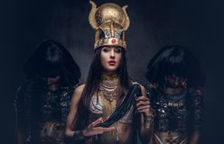 Portrait of haughty Egyptian queen in an ancient pharaoh costume with two concubines. Isolated on a dark background Stock Images