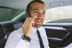 Portrait haut étroit d'un homme d'affaires bel invitant le téléphone intelligent et s'asseyant sur le siège arrière de voiture images stock