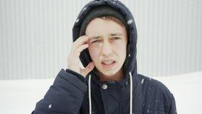 Portrait haut étroit d'un jeune homme dans la ville d'hiver avec la lésion oculaire, hémorragie banque de vidéos