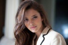 Portrait haut étroit d'une belle jeune femme d'affaires avec de longs cheveux de brune posant dans le costume élégant, regardant  images libres de droits