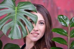 Portrait haut étroit d'une jeune dame de brune La pose de fille, regardant loin Les palmettes vertes entourent son visage images stock