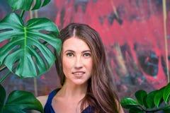 Portrait haut étroit d'une jeune dame de brune, robe bleue de port La pose de fille, regardant la caméra Paume verte photos libres de droits