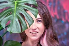 Portrait haut étroit d'une jeune dame de brune, robe bleue de port La pose de fille, regardant la caméra Paume verte images stock