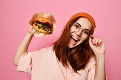 Portrait haut étroit d'une jeune femme affamée mangeant l'hamburger d'isolement au-dessus du fond rose photos libres de droits