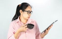 Portrait haut étroit de femme asiatique sûre, de verres de port et de tenir la tasse de café, regardant le comprimé avec regarder photo stock