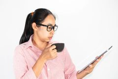 Portrait haut étroit de femme asiatique sûre, de verres de port et de tenir la tasse de café, regardant le comprimé avec regarder photos stock