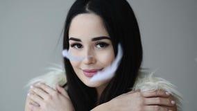 Portrait haut étroit de femme ouvrir son oeil avec des plumes tombant vers le bas maquillage banque de vidéos