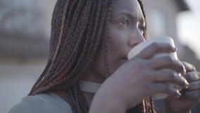 Portrait haut étroit de jeune femme de sourire noire d'afro-américain sûr avec la tasse de café chaude sur la rue lent banque de vidéos