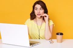 Portrait haut étroit de la jeune femelle de brune s'asseyant devant l'ordinateur portable, la femme avec le casque et le fonction photos libres de droits