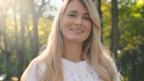 Portrait haut étroit de lumière du soleil debout de femme en parc d'automne Mouvement lent Fille de sourire merveilleuse avec un  banque de vidéos