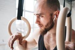 Portrait haut étroit de mâle de gymnaste prenant le repos après séance d'entraînement intense d'anneau d'immersion au gymnase images libres de droits