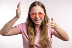 Portrait haut étroit de rire, femme heureuse dans des lunettes de soleil roses image stock
