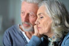 Portrait haut étroit des couples supérieurs tristes posant à la maison images stock