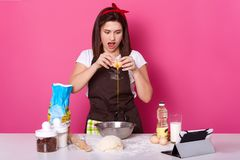 Portrait haut étroit des fracas de femme et oeuf de poinçons pour la préparation de gâteau Concept de la cuisson et de la pr images libres de droits