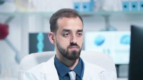 Portrait haut étroit du docteur masculin souriant à la caméra banque de vidéos