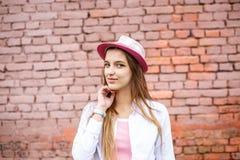Portrait haut ?troit de belle fille ?l?gante d'enfant dans le chapeau pr?s du mur de briques rose comme fond photo stock
