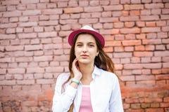 Portrait haut ?troit de belle fille ?l?gante d'enfant dans le chapeau pr?s du mur de briques rose comme fond photographie stock libre de droits